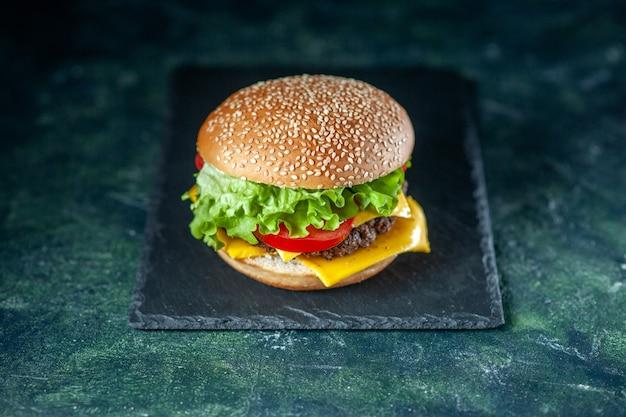 Vista frontal deliciosa hamburguesa de carne con ensalada de queso verde y tomates sobre fondo oscuro