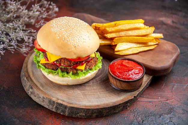 Vista frontal deliciosa hamburguesa de carne con papas fritas sobre fondo oscuro