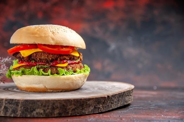 Vista frontal deliciosa hamburguesa de carne con queso sobre fondo oscuro