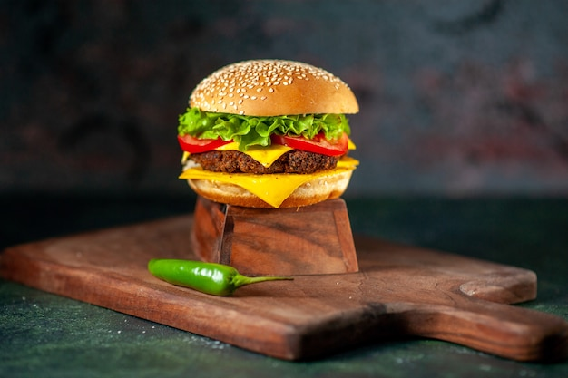 Vista frontal deliciosa hamburguesa con queso sobre fondo oscuro