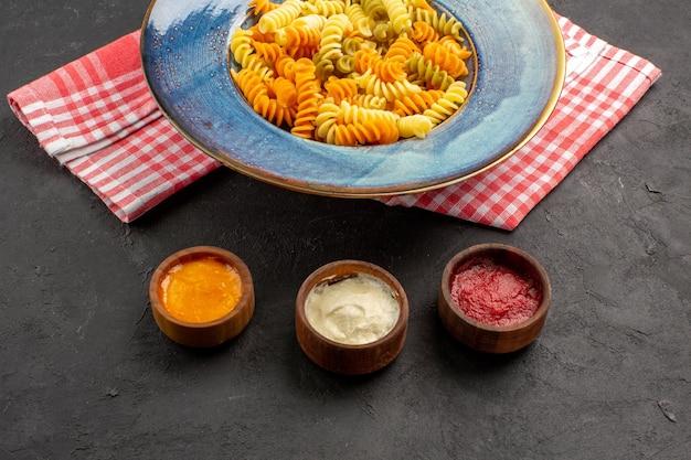Vista frontal deliciosa pasta italiana pasta espiral cocida inusual en un espacio oscuro