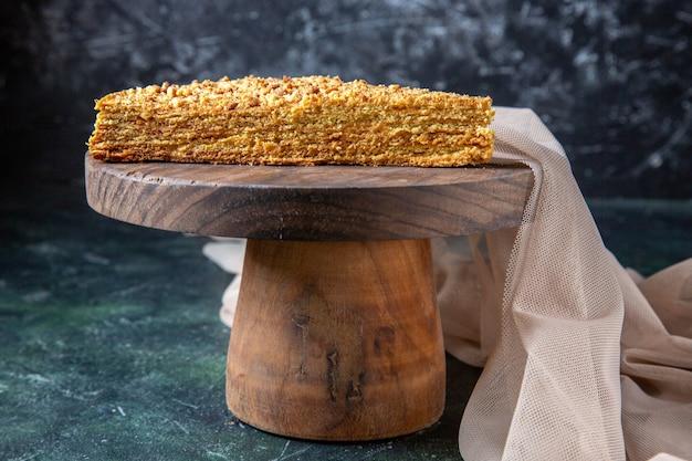 Vista frontal deliciosa rebanada de pastel de miel en la superficie oscura del tablero de madera redonda