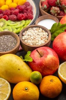 Vista frontal deliciosas frutas en rodajas dentro de la placa con frutas frescas en fruta oscura árbol de fotos maduras exóticas