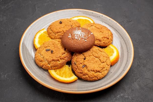 Vista frontal deliciosas galletas de azúcar con naranjas en rodajas dentro de la placa sobre el fondo oscuro galleta de azúcar fruta dulce galleta