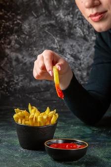 Vista frontal deliciosas papas fritas con condimentos que se comen por la superficie oscura femenina