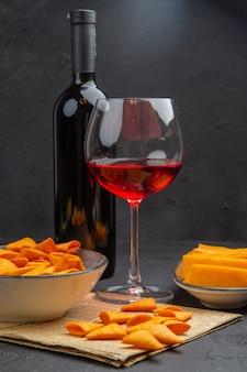 Vista frontal de deliciosas papas fritas dentro y fuera del tazón y vino tinto en un vaso sobre una vieja botella de periódico sobre un fondo negro
