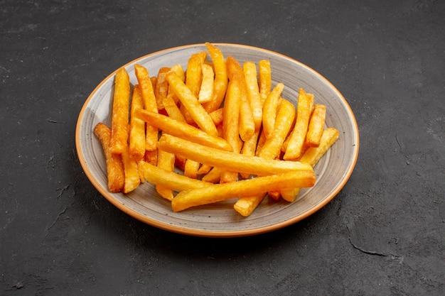 Vista frontal deliciosas papas fritas dentro de la placa en el espacio oscuro