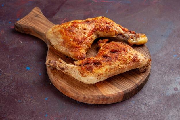 Vista frontal deliciosas rebanadas de carne cocida de pollo frito en el espacio oscuro