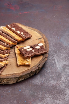 Vista frontal deliciosas rebanadas de pastel con nueces en un escritorio oscuro, té, galletas de azúcar, galleta, pastel de pastel dulce