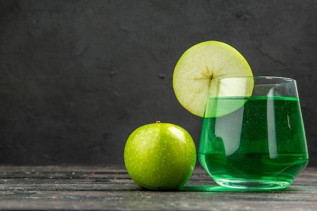 Vista frontal del delicioso jugo natural fresco en un vaso y manzanas verdes sobre fondo negro