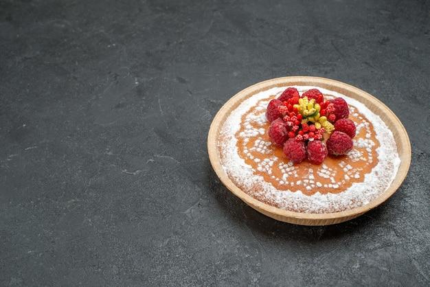 Vista frontal delicioso pastel con azúcar en polvo y frambuesas sobre fondo gris pastel pastel frutas baya galletas dulces