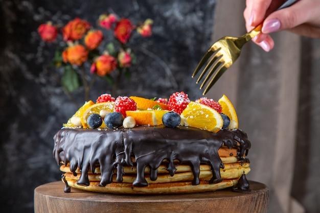 Vista frontal delicioso pastel de chocolate con frutas frescas en la pared oscura