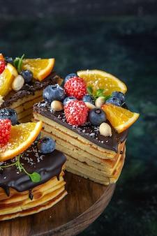 Vista frontal delicioso pastel de chocolate con frutas en la pared oscura