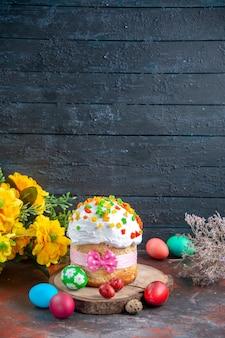 Vista frontal delicioso pastel de crema con frutos secos para pascua junto con huevos de colores sobre fondo oscuro color pascua étnica coloridas fiestas ornamentadas