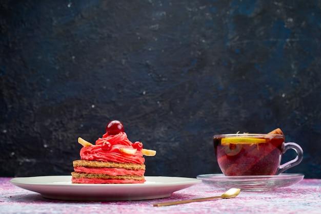 Vista frontal del delicioso pastel de crema con una taza de té en la superficie oscura