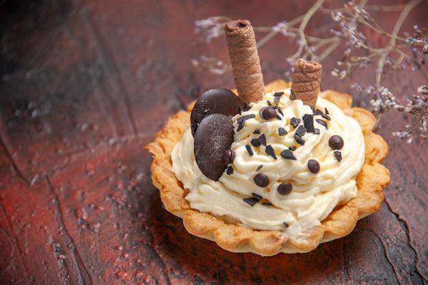 Vista frontal delicioso pastel cremoso sobre el fondo oscuro