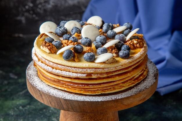 Vista frontal delicioso pastel con nueces, arándanos y galletas superficie oscura