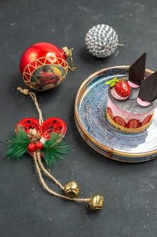 Vista frontal delicioso pastel de queso con fresa y chocolate en placa ovalada juguetes de árbol de navidad sobre fondo oscuro aislado
