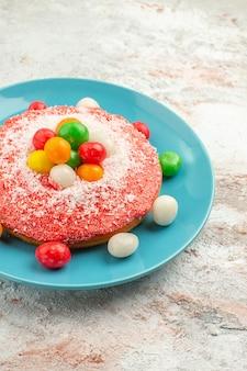 Vista frontal delicioso pastel rosa con caramelos de colores dentro de la placa sobre fondo blanco pastel de color arco iris pastel postre dulce