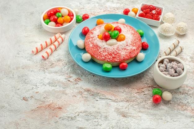 Vista frontal delicioso pastel rosa con caramelos de colores sobre fondo blanco pastel de golosinas arco iris de colores de postre dulce