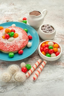 Vista frontal delicioso pastel rosa con caramelos de colores sobre fondo blanco postre color arco iris pastel de golosinas goodie