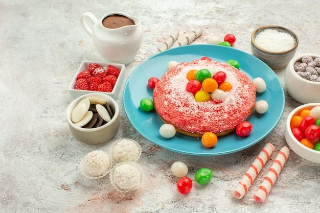 Vista frontal delicioso pastel rosa con caramelos de colores sobre fondo blanco postre golosina pastel de color arco iris caramelo