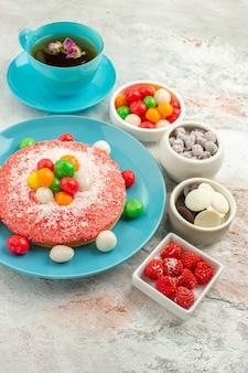 Vista frontal delicioso pastel rosa con caramelos de colores y una taza de té sobre fondo blanco pastel de postre pastel de color arco iris caramelo