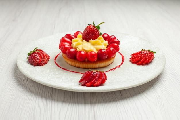 Vista frontal delicioso pastelito con frutas dentro de la placa en el escritorio blanco pastel postre fruta