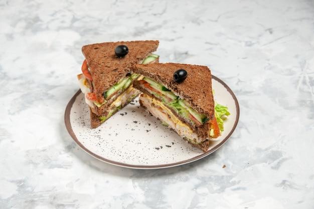 Vista frontal del delicioso sándwich con pan negro decorado con oliva en un plato sobre superficie blanca manchada