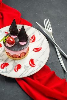 Vista frontal delicioso tarta de queso con fresa y chocolate en placa chal rojo cruzado cuchillo y tenedor sobre fondo oscuro aislado