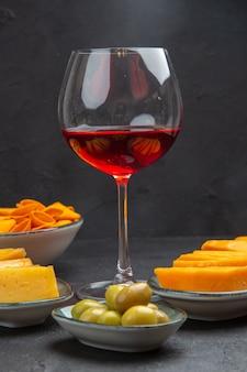 Vista frontal de deliciosos bocadillos para vino en una copa de vidrio sobre un fondo negro