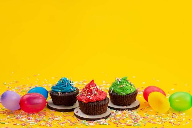 Vista frontal de deliciosos brownies a base de chocolate junto con caramelos y bolas de color amarillo, bizcocho de caramelo de color galleta