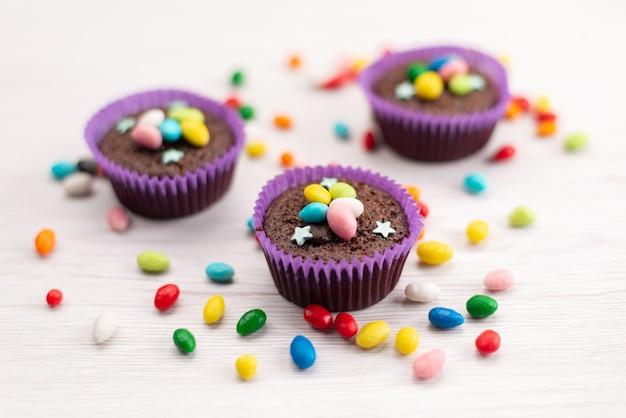 Una vista frontal de deliciosos brownies dentro de formas púrpuras con caramelos de colores sobre blanco, dulces de color caramelo