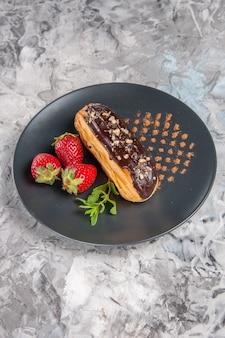 Vista frontal deliciosos canutillos de chocolate con fresas en la mesa de luz, postre, pastel, dulces