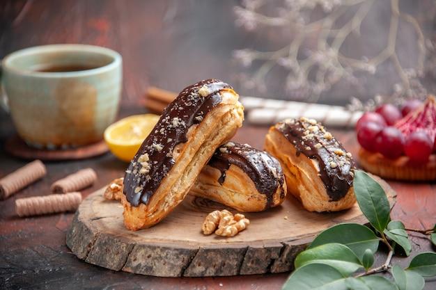 Vista frontal deliciosos canutillos de chocolate sobre el fondo oscuro