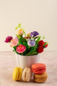 Una vista frontal deliciosos macarons franceses con flores en el escritorio rosa