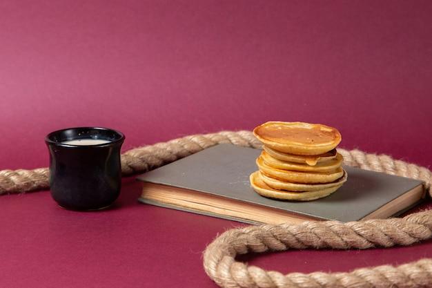 Vista frontal deliciosos panqueques en el cuaderno con una taza de leche sobre el fondo rosa, azúcar dulce, hornear, masa, desayuno