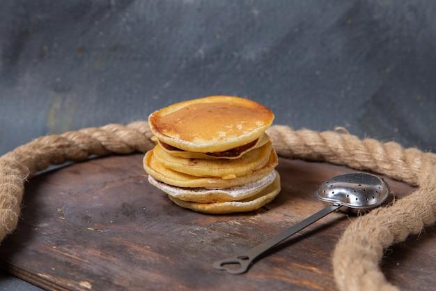 Vista frontal deliciosos panqueques con cuerdas en el fondo de madera, azúcar dulce, comida, desayuno