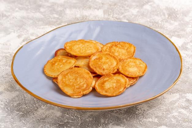Vista frontal deliciosos panqueques dulces dentro de la placa azul en el escritorio gris comida de panqueques postre dulce