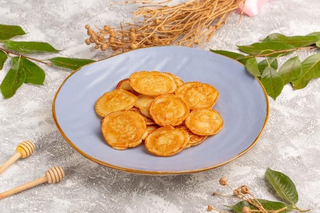 Vista frontal deliciosos panqueques dulces dentro de la placa azul en la superficie gris comida de panqueques postre dulce