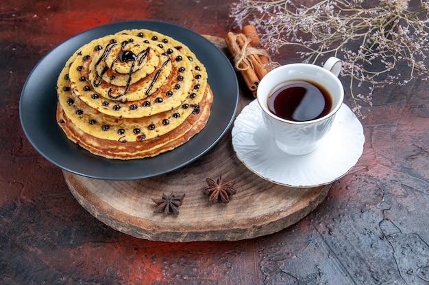 Vista frontal deliciosos panqueques dulces con taza de té sobre fondo oscuro pastel dulce postre leche