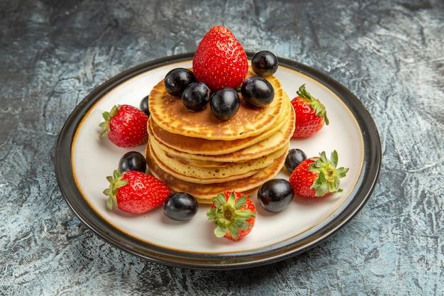 Vista frontal deliciosos panqueques con frutas y bayas en el postre de pastel de frutas de piso oscuro