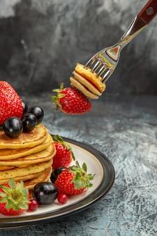 Vista frontal deliciosos panqueques con frutas y bayas en la superficie oscura pastel de frutas de postre