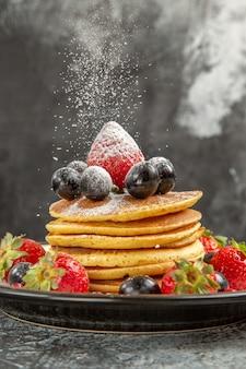 Vista frontal deliciosos panqueques con frutas frescas en la superficie ligera desayuno fruta dulce
