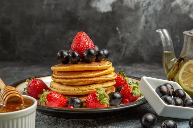 Vista frontal deliciosos panqueques con frutas frescas en la superficie de la luz pastel dulce de frutas