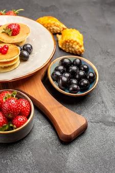 Vista frontal deliciosos panqueques con frutas en pastel de superficie oscura pastel dulce de frutas