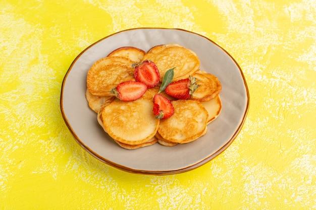 Vista frontal deliciosos panqueques horneados dentro de la placa marrón con rodajas de fresas en la mesa amarilla comida para panqueques fruta baya postre dulce