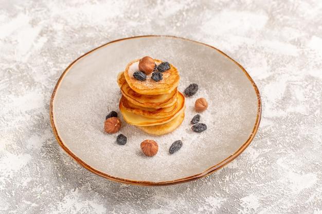 Vista frontal deliciosos panqueques poco con nueces dentro de la placa en la superficie gris claro panqueques comida dulce desayuno
