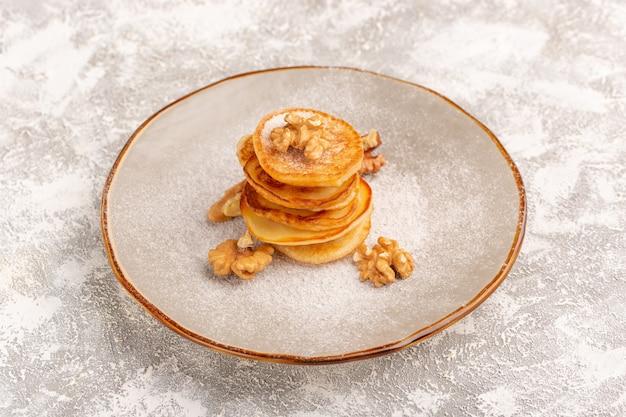 Vista frontal deliciosos panqueques poco con nueces dentro de la placa en la superficie de luz gris panqueques dulces comida desayuno