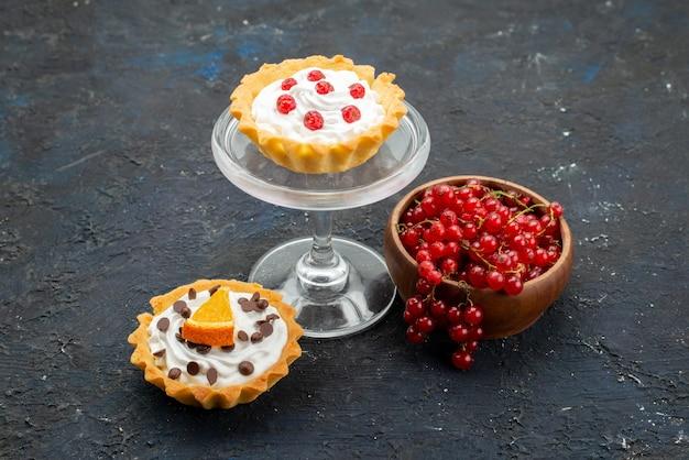 Vista frontal deliciosos pasteles con crema y frutas sobre la superficie oscura dulce